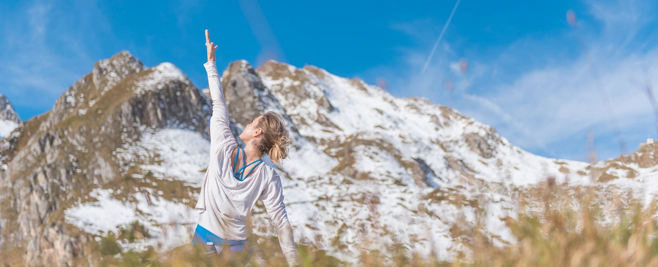 Yoga Übungen vor der schneebedeckten Gasteiner Bergwelt
