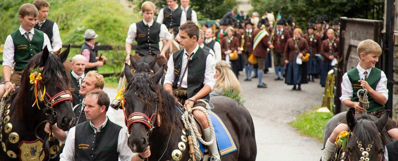 Kinder in Tracht auf Pferden, geführt von Aufsichtspersonen