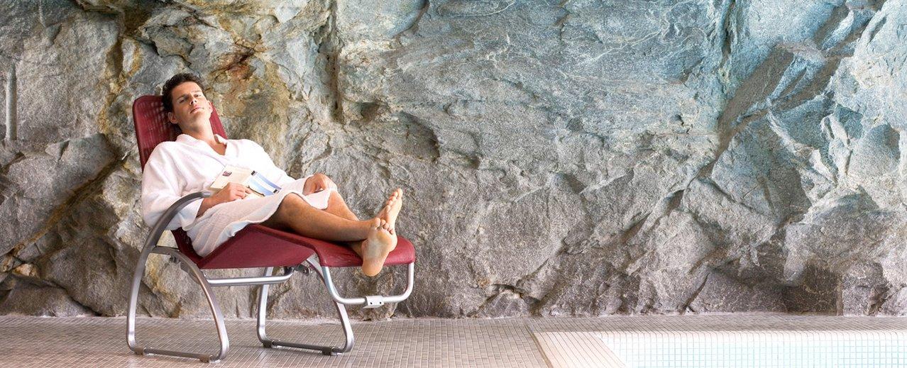 Mann beim Entspannen auf einer Liege vor der Felswand im Innenbereich der Felsentherme