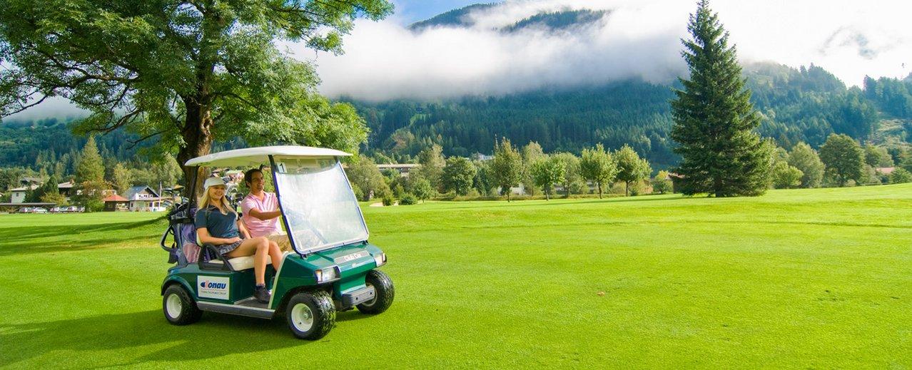 Golfer am Weg mit dem Golf Cart