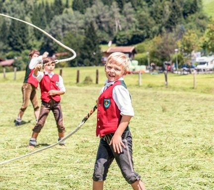 Kinder in Tracht die ein Seil schwingen